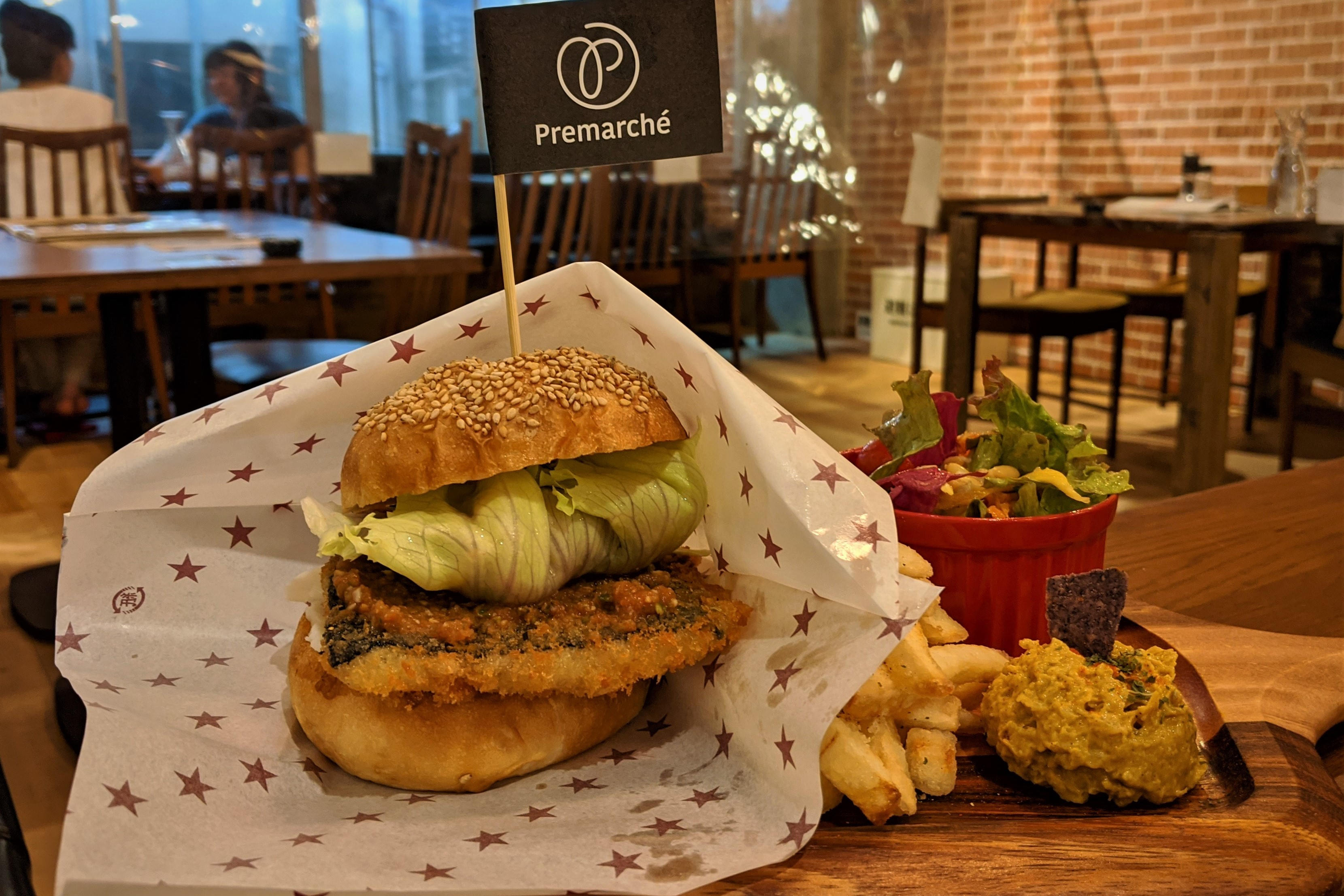 vegetarian burger wrapped in paper with a side of chips and salad on a wooden table